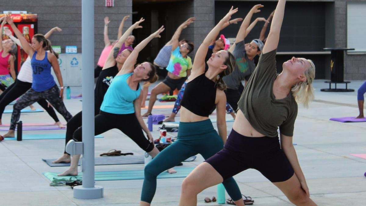 Guests in workout clothes follow instructor doing yoga on the Sun Deck
